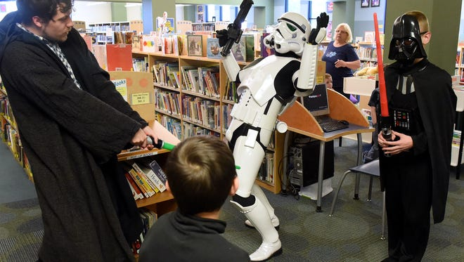 "Jedi knight Ben Thomas of Augusta Public Library strikes down Imperial Stormtrooper TK-487, aka. Matthew Nargi, of the Garrison Tyranus of the 501st Legion as Lord Darth Vader, portrayed by 12-year-old Justin Riddle of Verona, stands ready during a mock battle. The Augusta County Library held a Star Wars ""May the 4th be with you"" celebration at their Fishersville branch on Monday, May 4, 2015. The event was also held at their Churchville branch."
