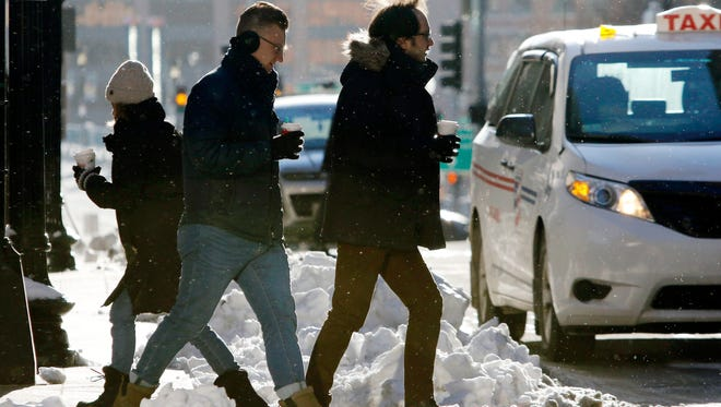 Pedestrians cross the street as the temperature hovers in the single-digits, Thursday, Dec. 28, 2017, in downtown Boston.
