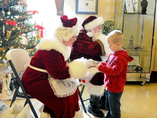 Mrs. Claus gives a treat bag to a visitor after he