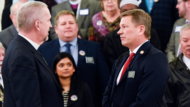 Bishop David B. Zellmer (left) of the Evangelical Lutheran Church in America speaks to Sen. Neal Tapio (right) after Tapio interrupted a gathering between lawmakers and an interfaith coalition on Wednesday, Jan. 10, 2017 in the capitol building in Pierre, S.D.