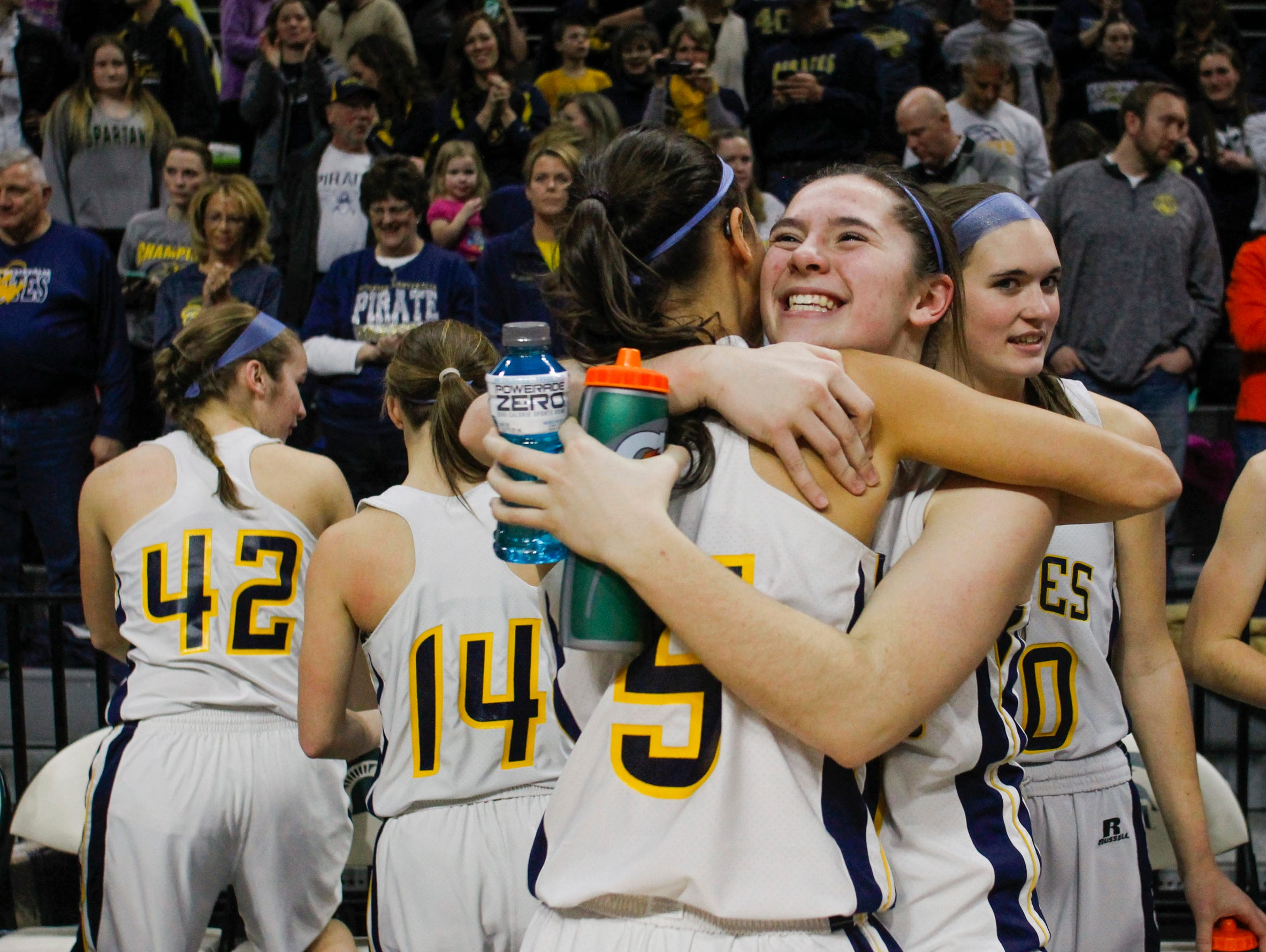 Pewamo-Westphalia 's Kylen Pohl hugs teammate Kiera Thelen, right, after the Pirates beat Maple City Glen Lake Thursday, March 16, 2017, during the Class B Semifinal at the Breslin in East Lansing. P-W won 64-51.