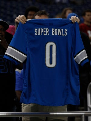 A fan holds up a Lions jersey after the team's 42-17 loss to the Cardinals at Ford Field on Oct. 11, 2015