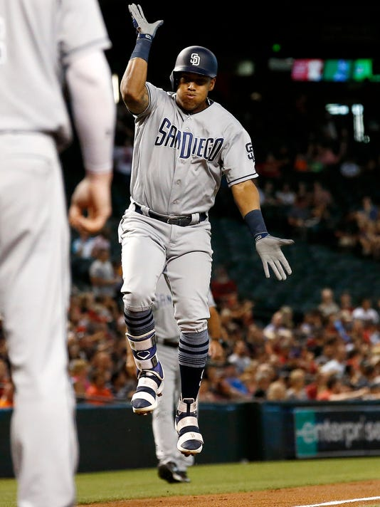 San Diego Padres' Yangervis Solarte jumps and claps after his home run against the Arizona Diamondbacks, before stepping on home plate during the first inning of a baseball game Wednesday, June 7, 2017, in Phoenix. (AP Photo/Ross D. Franklin)