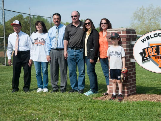 Former Pitman High School baseball coach Joe Lang, far left, is joined by members of his family as he stands by the new sign at Pitman High School baseball field, which is dedicated to Lang.