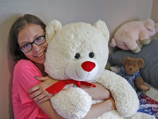 Scarlet hugs a large stuffed bear in her room at her