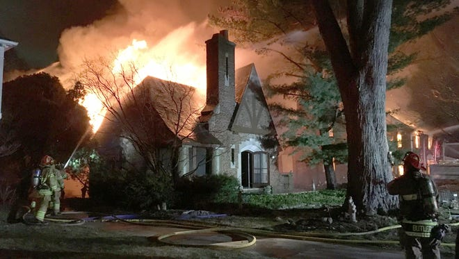 Fire crews battle a house fire on Washington Road, between Kercheval and Waterloo, in the city of Grosse Pointe on Monday, March 26, 2018.