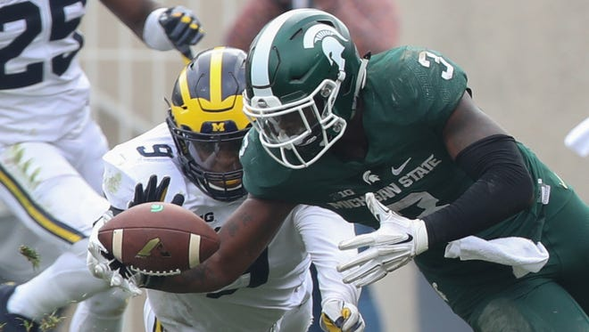 Michigan LB Mike McCray goes for the loose ball against Michigan State RB LJ Scott in the fourth quarter Oct. 29, 2016 at Spartan Stadium in East Lansing.