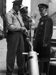 Guards Raymond Quade (left) and Thaddeus Wishowski wheel a coin-collecting receptacle by Patrolman Phillip Weinheim as they collected proceeds from the first day of operations of Milwaukee's first parking meters on Dec. 19, 1949. A total of $342.53 was found in the meters the first day. The photo was published on the front page of the Dec. 19, 1949, Milwaukee Journal.