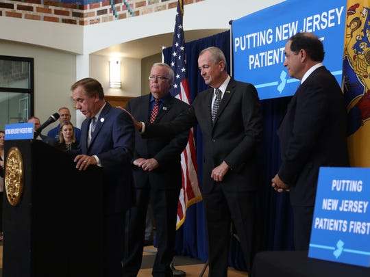 Assembly speaker Craig Coughlin  addresses the audience of supporters for the bill to prevent surprise medical bills for out-of-network consumers. Woodbridge Mayor John McCormac, Governor Phil Murphy and Senator Joseph Vitale look on.