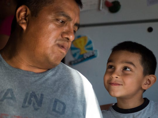 Abdiel Librado, 5, looks up at his father, Alberto, in their kitchen in White Pine, Tenn., on July 3, 2018. Alberto Librado was detained by U.S. Immigration and Customs Enforcement agents when they raided the Southeastern Provision meat-packing plant where he worked outside Bean Station.