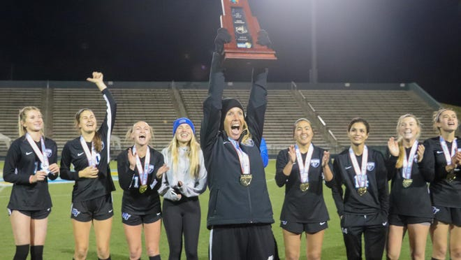 Bartram Trail soccer coach Jen Rodriguez holds the FHSAA state championship trophy aloft after leading the Bears to the first state title in program history last season. Bartram Trail goes for the Class 7A repeat Friday at 1 p.m. in DeLand against Weston Cypress Bay in a rematch from last year.