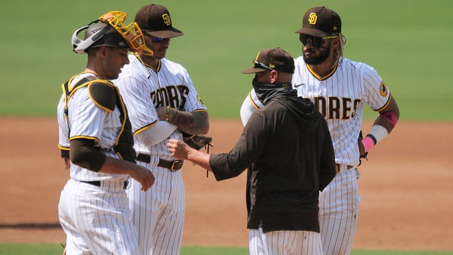 San Diego Padres manager Jayce Tingler, middle, talks with catcher Jason Castro, left, Manny Macho, middle, and Fernando Tatis Jr., right, during a pitching change against the Los Angeles Dodgers in the third inning of a baseball game Wednesday, Sept. 16, 2020, in San Diego. (AP Photo/Derrick Tuskan)