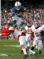 Penn State's Saquon Barkley (26) hurdles Rutgers' Kiy