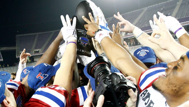 Louisiana Tech Bulldogs players hold up the championship trophy after the game against the Navy Midshipmen at Amon G. Carter Stadium. Louisiana Tech won 48-45.