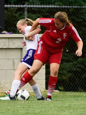 Mary Miller, left, of Fremont Ross fights Port Clinton's Maddy Gerwin for the ball on Wednesday.