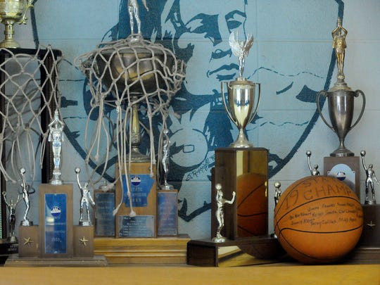 Shown is the Cotter Junior Warriors' 1965 state championship trophy, center, and championship ball signed by team members, right, that still sit prominently in the trophy case at Cotter High School.