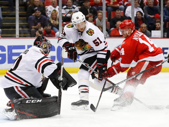 Blackhawks defenseman Brian Campbell (51) defends Red Wings right wing Gustav Nyquist (14) as goalie Corey Crawford, left, blocks a shot in the second period of the Wings' 4-2 win Friday at Joe Louis Arena.