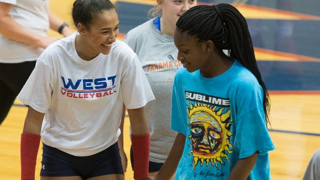 West Henderson's America Anderson, right, Deija Jackson, left, and McKenna Daley share a laugh during a recent practice at West.