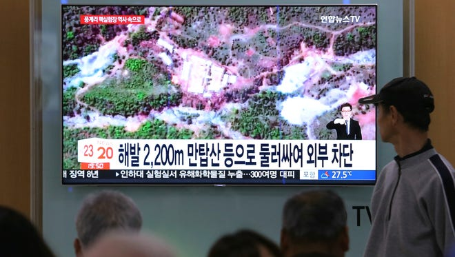 People watch a TV screen showing a satellite image of the Punggye-ri nuclear test site in North Korea during a news program at the Seoul Railway Station in Seoul, South Korea, Thursday, May 24, 2018.