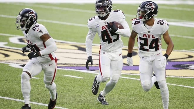Atlanta Falcons linebacker Deion Jones, center, returns an interception with teammates Kendall Sheffield, left, and A.J. Terrell, right, during the first half of an NFL football game against the Minnesota Vikings, Sunday, in Minneapolis.