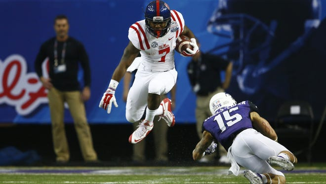Mississippi running back Mark Dodson (7) leaps over TCU safety Steve Wesley (15) during the first half of the Peach Bowl NCAA football game, Wednesday, Dec. 31, 2014, in Atlanta. (AP Photo/John Bazemore)