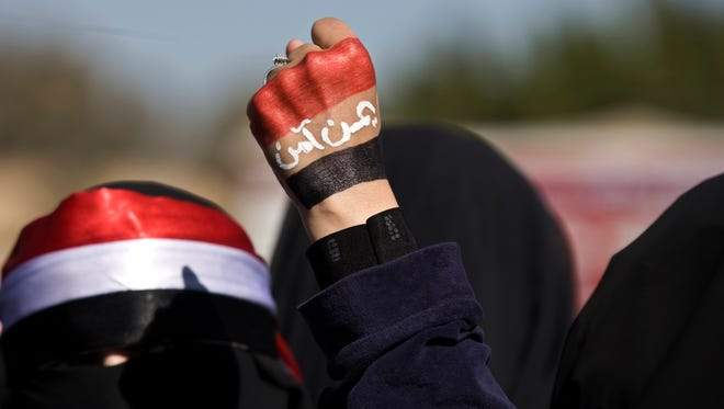 "A woman raises her fist painted with Yemen's flag and Arabic writing that reads, ""Yemen is safe,"" to protest against the Houthi Shiite rebels who hold the capital, Sanna, during a demonstration in Sanaa on Saturday, Jan. 24."