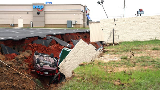 This photo shows vehicles after a cave-in of a parking lot in Meridian, Miss., Sunday, Nov. 8, 2015. Experts are to begin work Monday seeking to determine the cause of the Saturday collapse, authorities said.