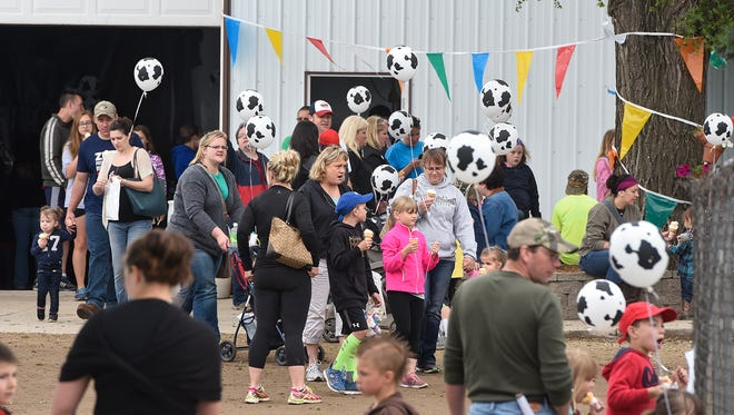 Visitors walk between buildings Saturday, June 4, 2016, during the Stearns County Breakfast on the Farm at Janski Farms near South Haven.