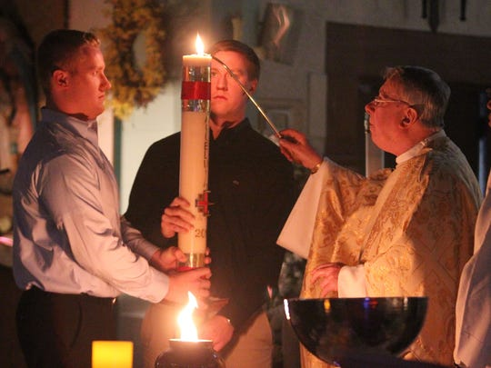 In this file photo from April 7, 2012, Monsignor John O'Keefe, right, lights a candle during the the Easter vigil at Saint Margaret of Antioch Catholic Church in Pearl River.