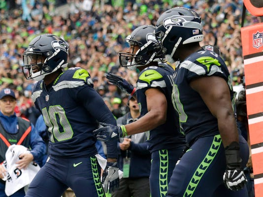 Seattle Seahawks wide receiver Paul Richardson, left, is greeted by teammates Tyler Lockett, center, and Rees Odhiambo, right, after Richardson caught a pass for a touchdown against the San Francisco 49ers in the second half of an NFL football game, Sunday, Sept. 17, 2017, in Seattle. (AP Photo/John Froschauer)
