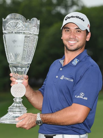 Jason Day of Australia poses with the winner's trophy