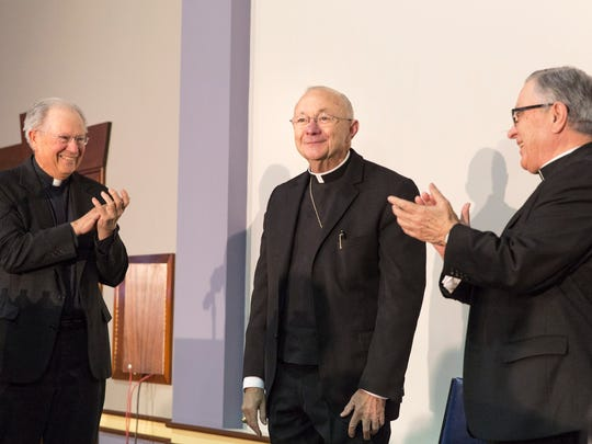 Rev. Richard Green left, and outgoing Bishop Michael Jarrell, right, greet Rev. J. Douglas Deshotel  during a press conference announcing him as the new Bishop of Lafayette.