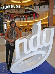 Former Ben Davis basketball standout, Fever player and now a stylist,  Shyra Ely-Gash stands by an INDY sign at Bankers Life Fieldhouse.