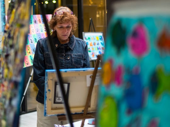 Lynne Clyma of East Lansing looks over the children's artwork to see what pieces she wants to bid on at the Art for Charlie event held Sunday at the East Lansing Marriott.