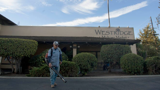 Feliciano Lazaro, with Mar Landscape, uses a leaf blower to clean up the parking lot of the Westridge Midtown Market in Ojai.
