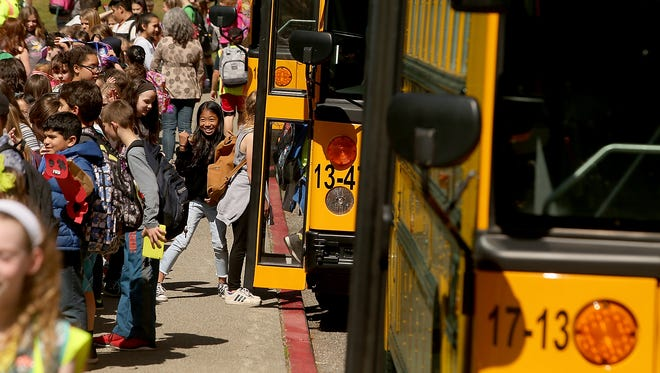 Students fill the sidewalk as they prepare to embark buses at the end of the school day at Poulsbo Elementary School on Wednesday. North Kitsap School District has been piloting software that tracks bus information, including location along the bus route.