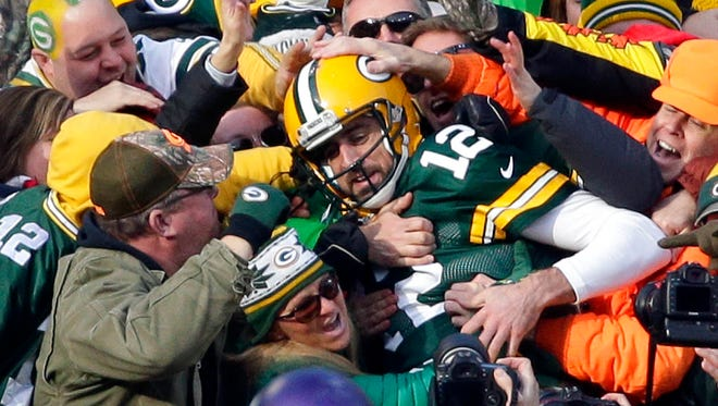 Green Bay Packers quarterback Aaron Rodgers (12) is swarmed by fans after scoring a touchdown in the first half during the game against Minnesota on Saturday, December 24, 2016 at Lambeau Field.