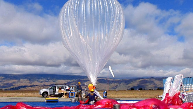 Google employees fill a Raven Aerostar high-altitude balloon with helium for a Project Loon launch.