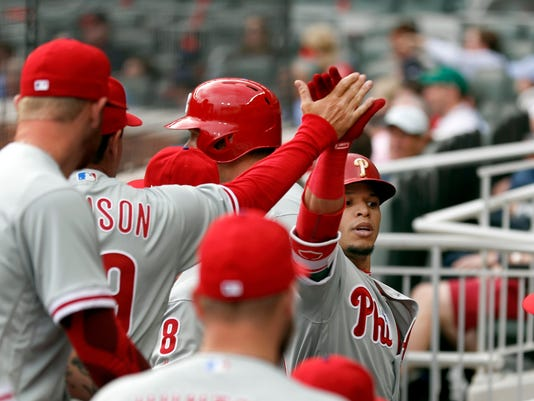 Philadelphia Phillies' Cesar Hernandez, right, celebrates in the dugout after hitting a home run in the sixth inning of a baseball game against Atlanta Braves, Thursday, March 29, 2018, in Atlanta. (AP Photo/John Bazemore)