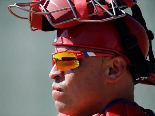 A practice field is reflected in the sunglasses of Philadelphia Phillies catcher Carlos Ruiz during a spring training baseball workout, Thursday, Feb. 19, 2015, in Clearwater, Fla. (AP Photo/Lynne Sladky)