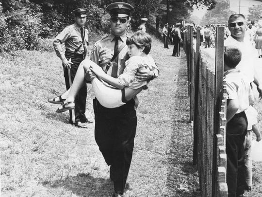 A state trooper assists a young girl who was overcome by heat and excitement during the Hollybush Summit in Glassboro in 1967.
