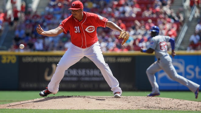 Cincinnati Reds starting pitcher Alfredo Simon (31) commits a fielding error to allow Chicago Cubs' Matt Szczur (not shown) to reach first as Cubs' Jorge Soler, right, runs safely to second in the third inning of a baseball game, Sunday, April 24, 2016, in Cincinnati. (AP Photo/John Minchillo)