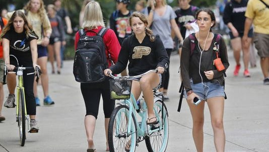Bicyclists and pedestrians maneuver around each other recently outside the Class of 1950 Lecture Hall on the Purdue University campus. There has been a 10 percent increase in freshman applications compared to last year.