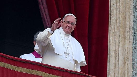 Pope Francis waves to the faithful as he delivers the traditional Urbi et Orbi Christmas Day message from the central balcony of St. Peters Basilica in Vatican City.