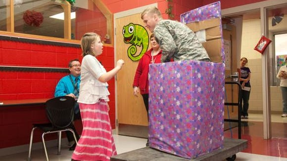 A surprised Andrea Miracle, 10, gets her Christmas wish as her only sibling, Jacob Miracle, pops out of a box in her Bullitt County class.