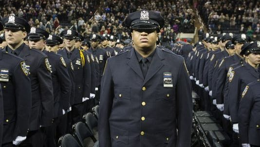 New recruits stand at attention while wearing bands over their badges in honor of deceased officers Rafael Ramos and Wenjian Liu during a New York Police Academy graduation ceremony Monday at Madison Square Garden in New York.