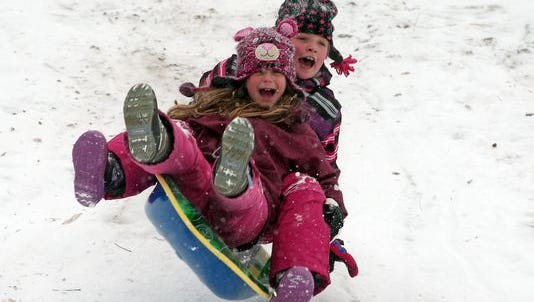 Julia West, 9, and Ellie Bozzo, 9, of Basking Ridge sled down a hill at the Oak Street School in Basking Ridge. January 26, 2015.