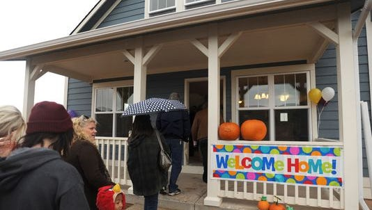 Visitors stop by a newly completed Habitat for Humanity home in Fort Collins.