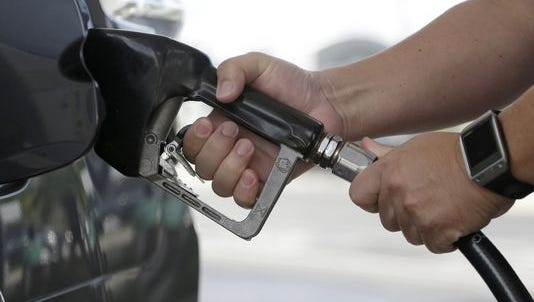 A motorist puts fuel in his vehicle.
