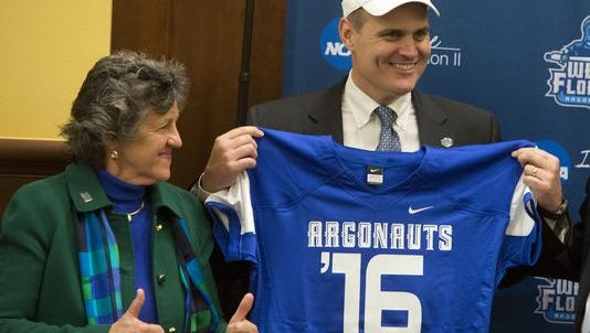University of West Florida President Judy Bense, left, and new football coach Pete Shinnick show off the Argos football jerseys. Shinnick and his staff are working on locking up the first class of signees for UWF football